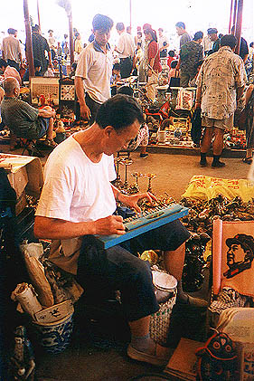 A man in market playing a very strange musical instrument to an image of Mao Zedong